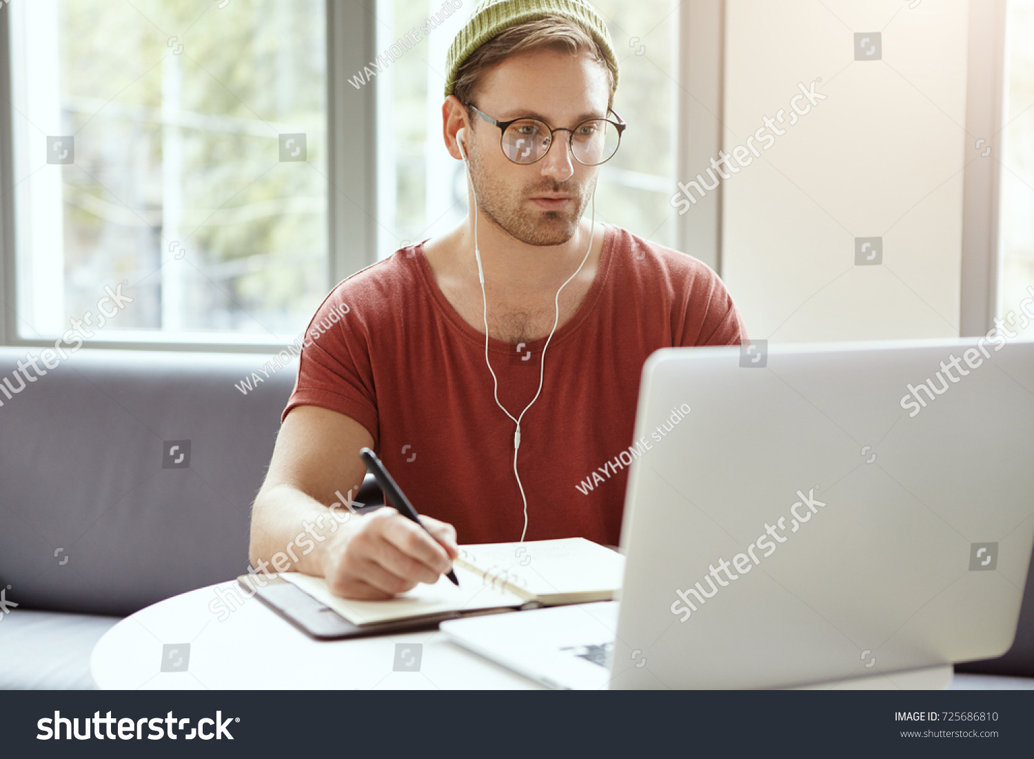 Concentrated bearded young European hipster in stylish round glasses and green hat looking at laptop screen and making notes in copybook while learning online, watching webinar using earplugs #725686810