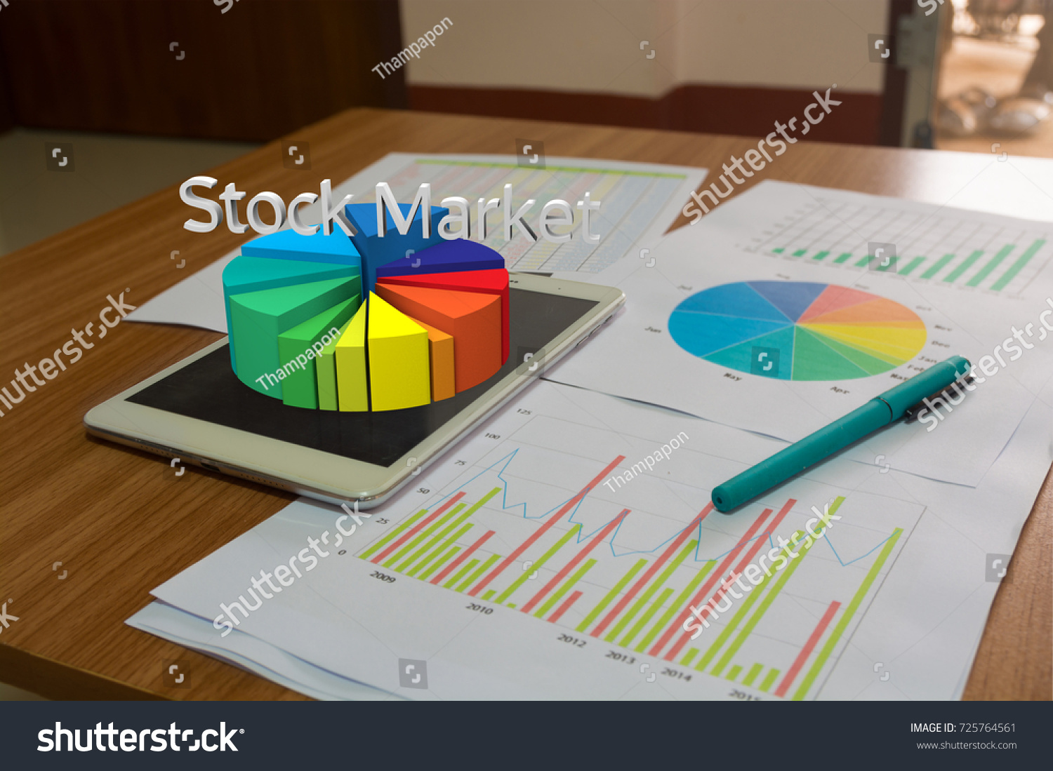 stock photo wireless tablet pc on wooden desk with stock market report bar chart pie diagram and pen as 725764561 wireless tablet pc on wooden desk stock photo (edit now) 725764561
