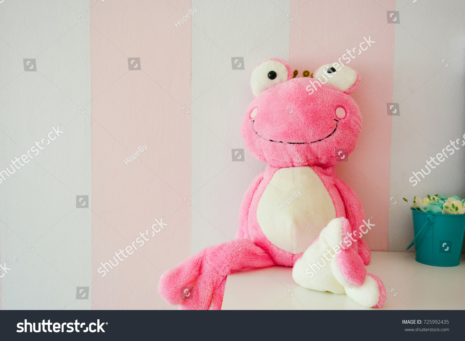 Frog doll over pink and white wall.