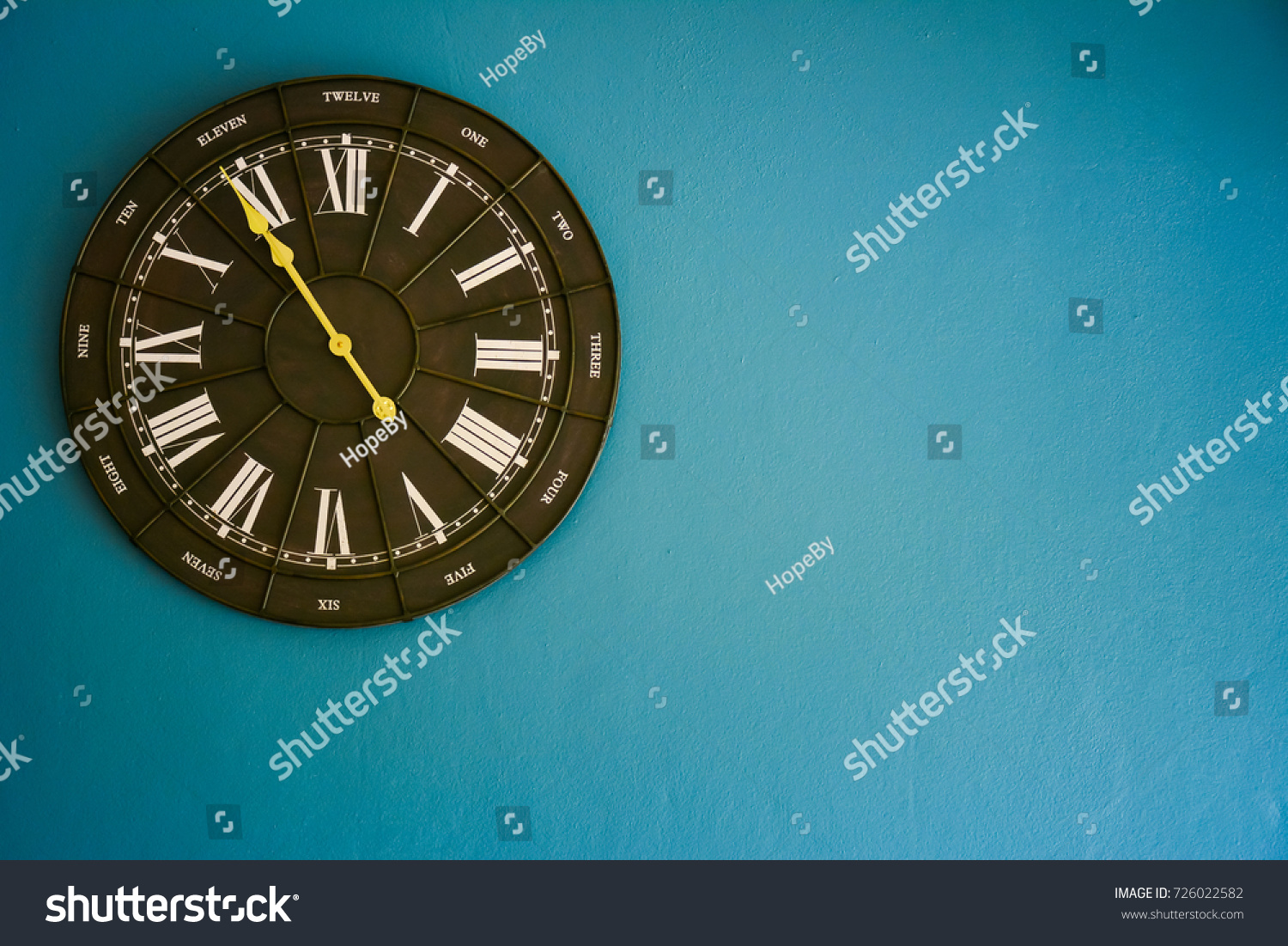 Analog vintage clock over blue wall.
