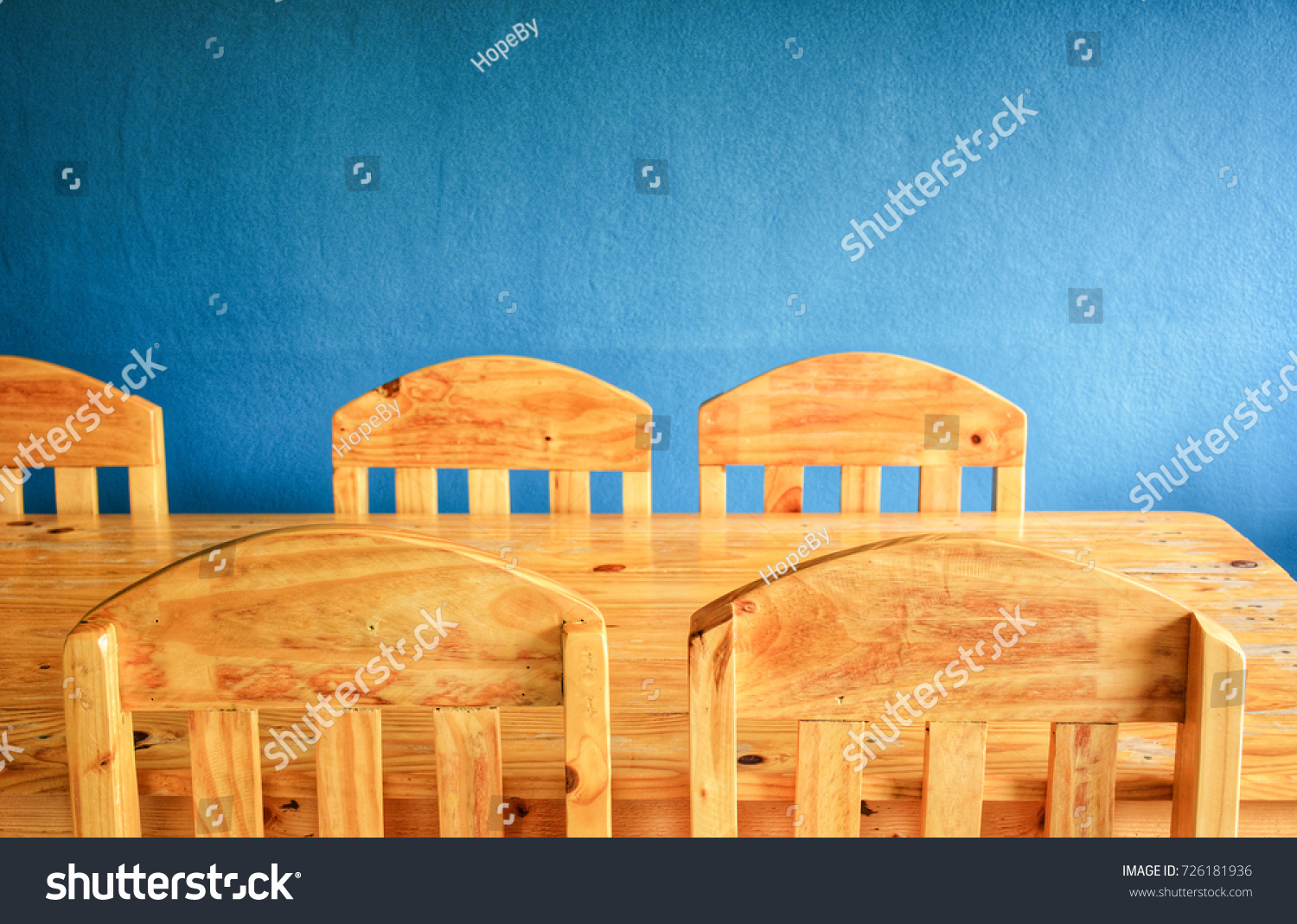 Wooden dinning table set over blue wall. Vintage style.