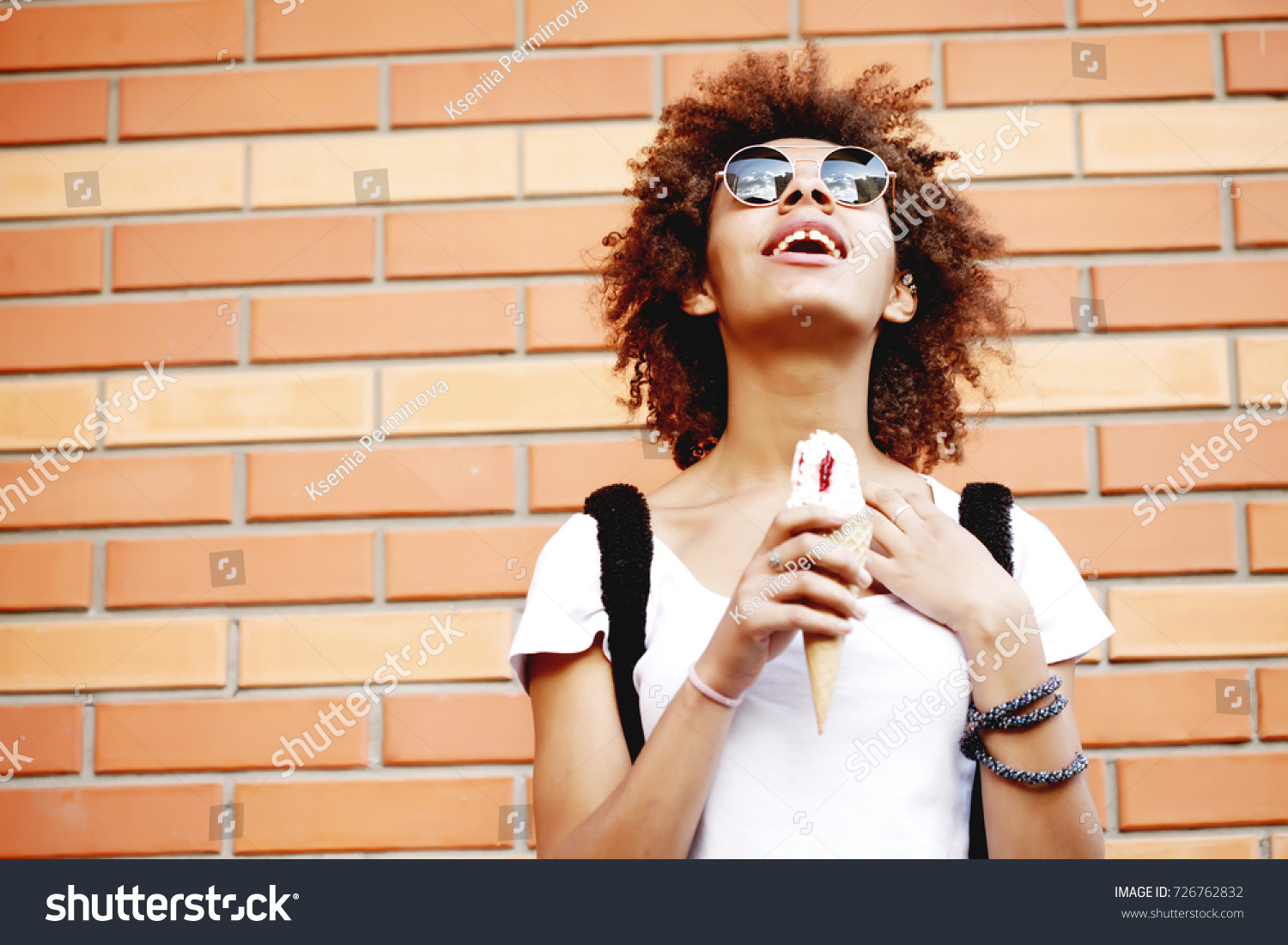 Outdoor closeup fashion portrait of afro american hipster teen crazy girl  eating ice cream in summer