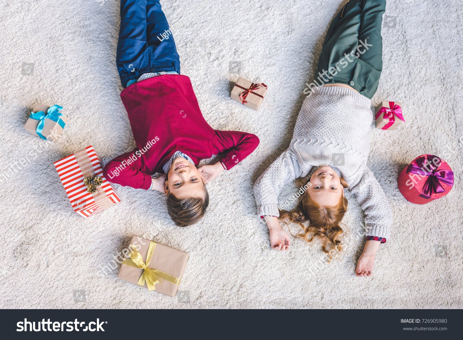 little brother and sister relaxing on floor with christmas gifts