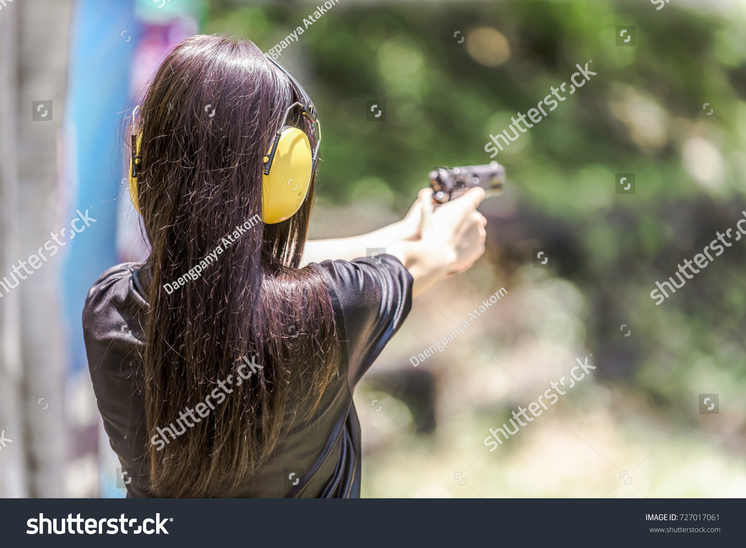 f8ee57bf77fd5 Woman aiming pistol at target out indoor firing range or shooting range.