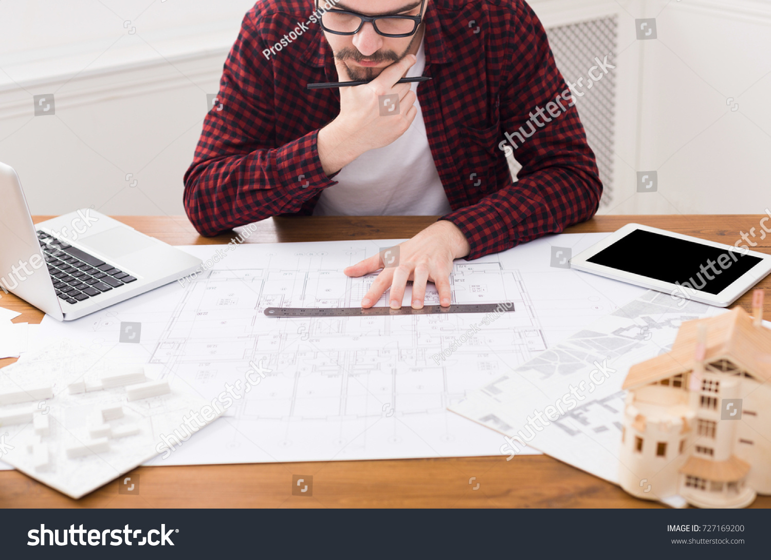 Designer working on blueprint office thoughtful stock photo designer working on blueprint in office thoughtful architect drawing building plan copy space malvernweather Images