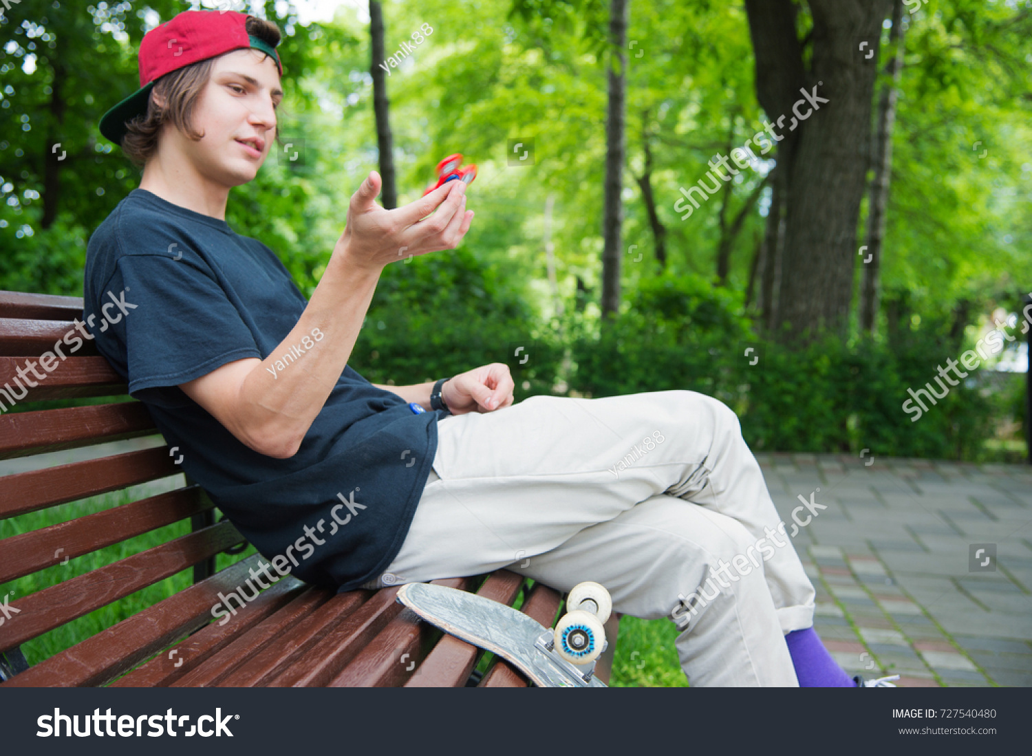 406c04dd9a1 Long-haired hipster skater in a cap sits on a bench and spins on a