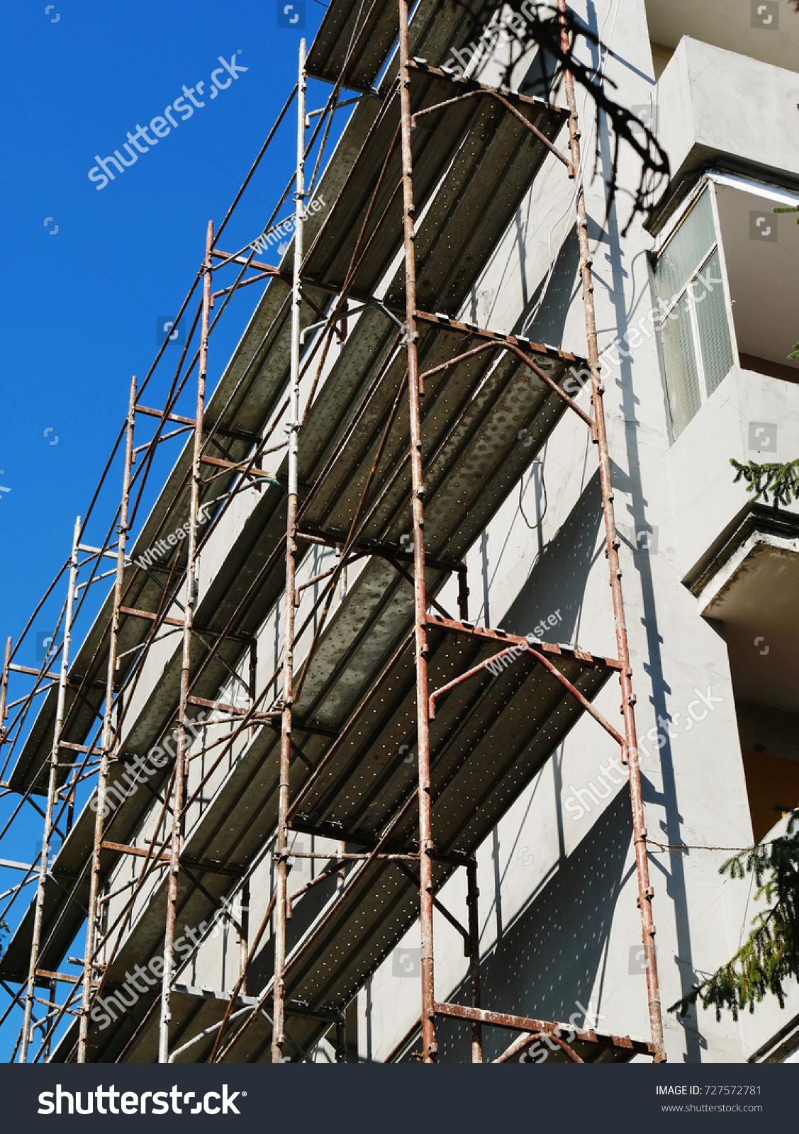 Block Of Flats Undergoing Exterior Renovation Work. Metallic Scaffolding Is  Raised Near Building Wall.