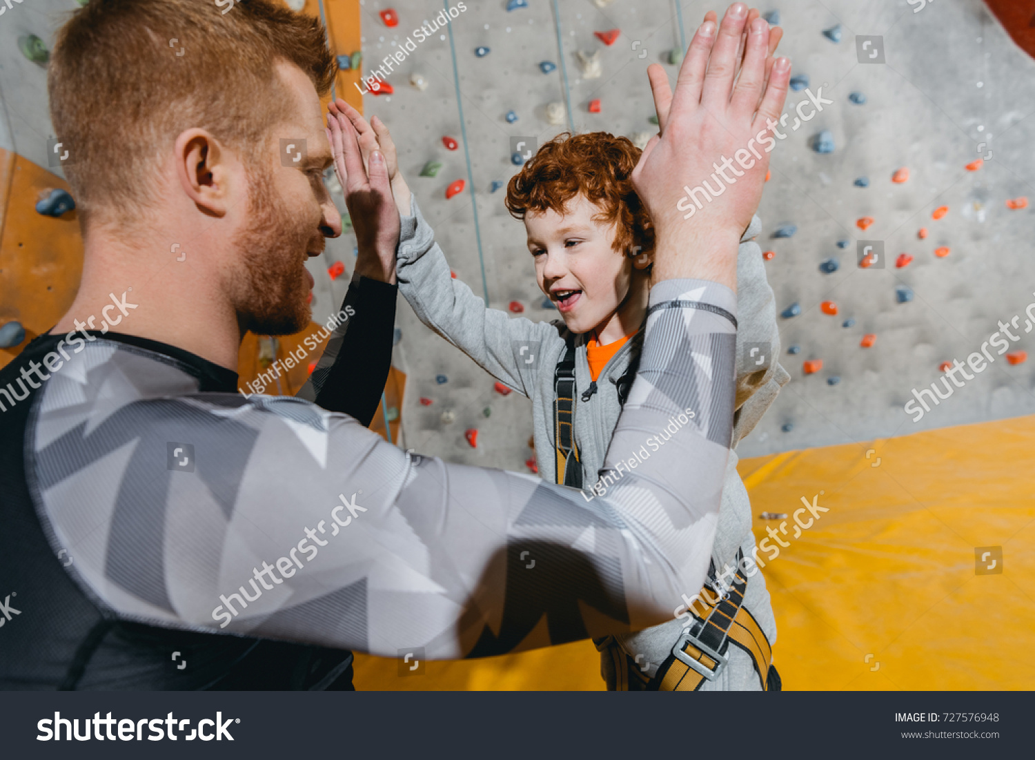 stock photo closeup shot of little boy in harness high fiving his dad with climbing walls in the bacackground 727576948 closeup shot little boy harness highfiving stock photo (edit now