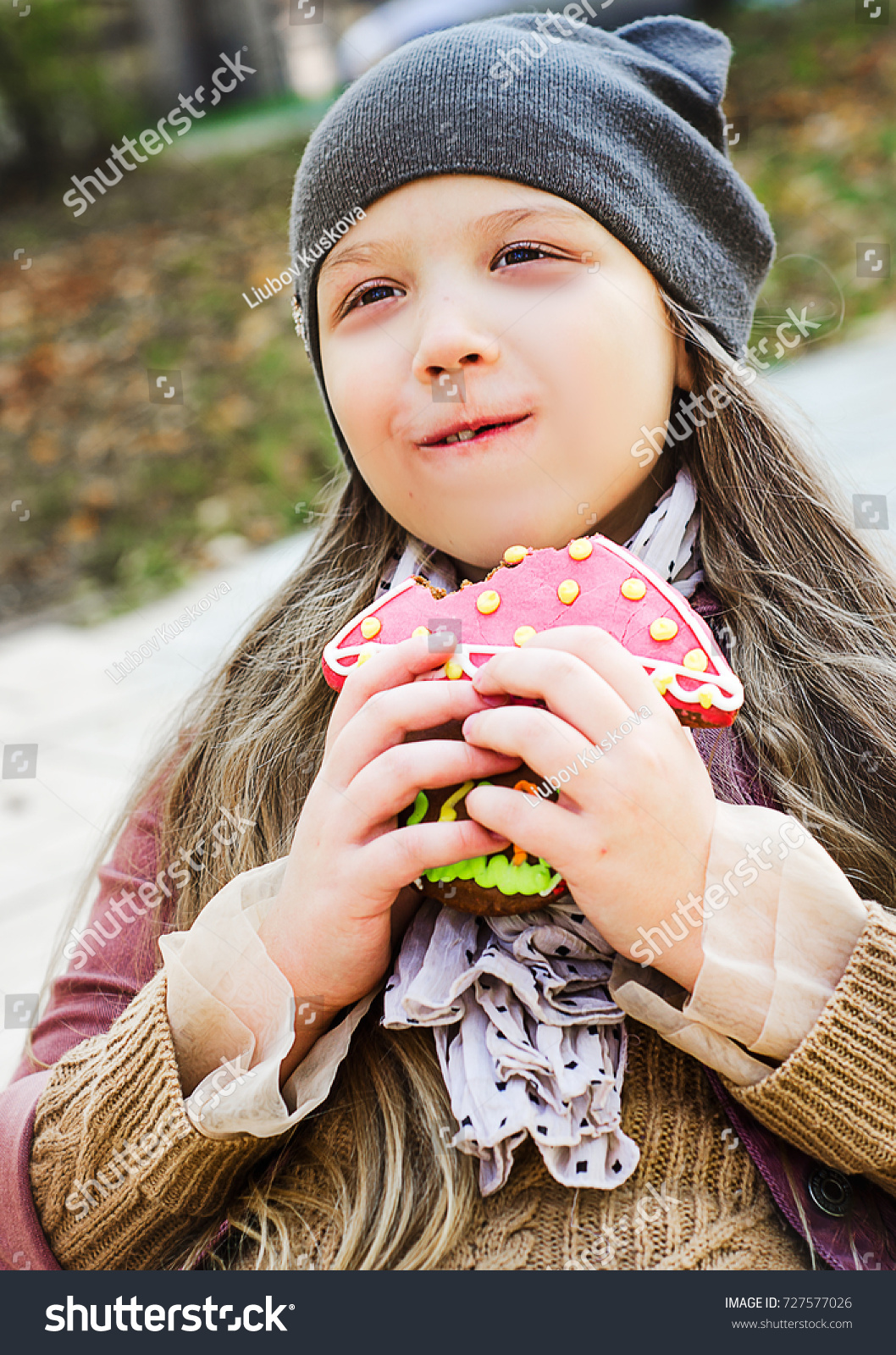 9563faa87bd Beautiful little smiling girl with long hair in knit hat with cats ears  eating honey cake