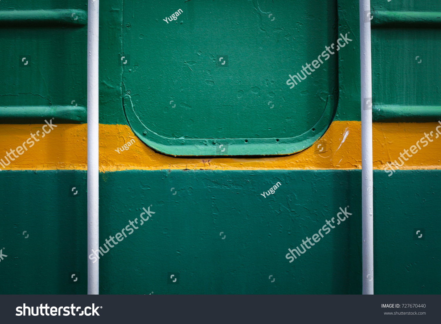 The handrails near the door to the train. Paint smudges on the surface. The green background. Painted metal surface. The yellow line on a green background. Metal painted green.