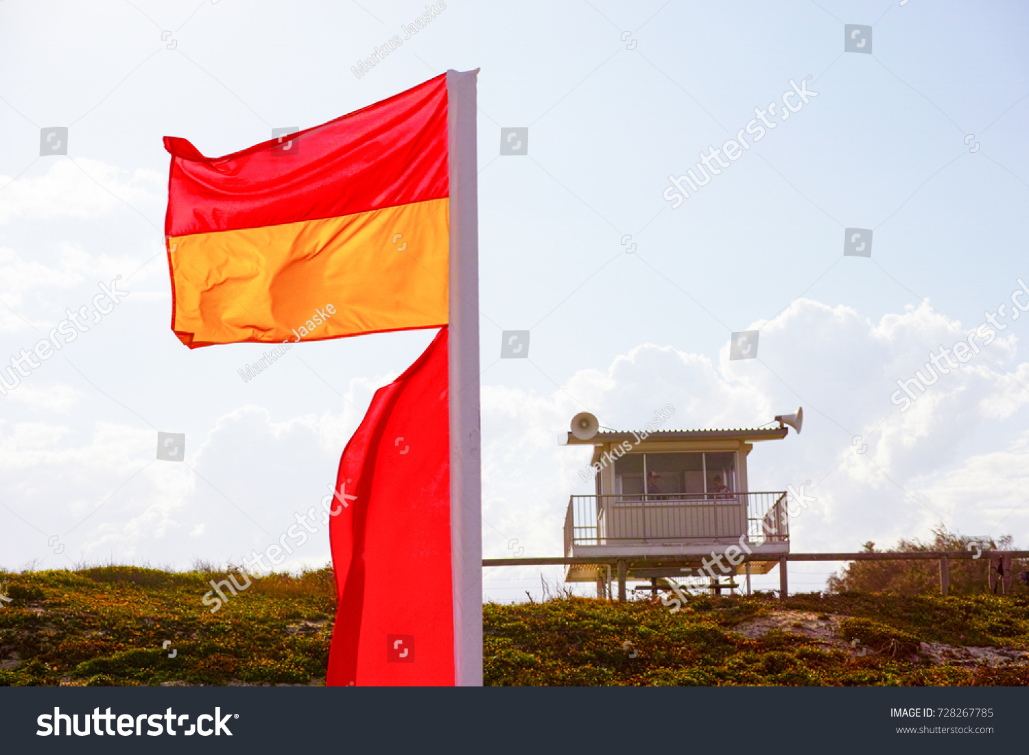 Beach flags and lifeguard tower overlooking australian beach red and yellow flag lifesaver signs