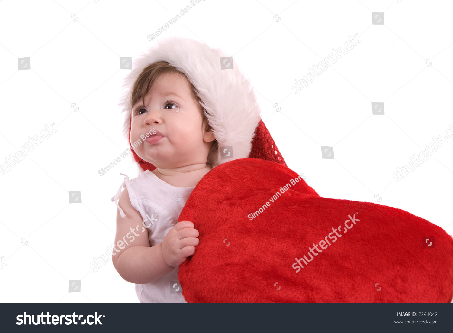 Cute little baby wearing a santa hat and holding on to a large red heart 7f8fc18a97a