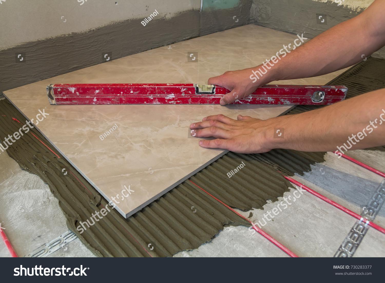 Workers hands ceramic tiles tools tiler stock photo 730283377 workers hands with ceramic tiles and tools for tiler floor tiles installation home improvement dailygadgetfo Image collections