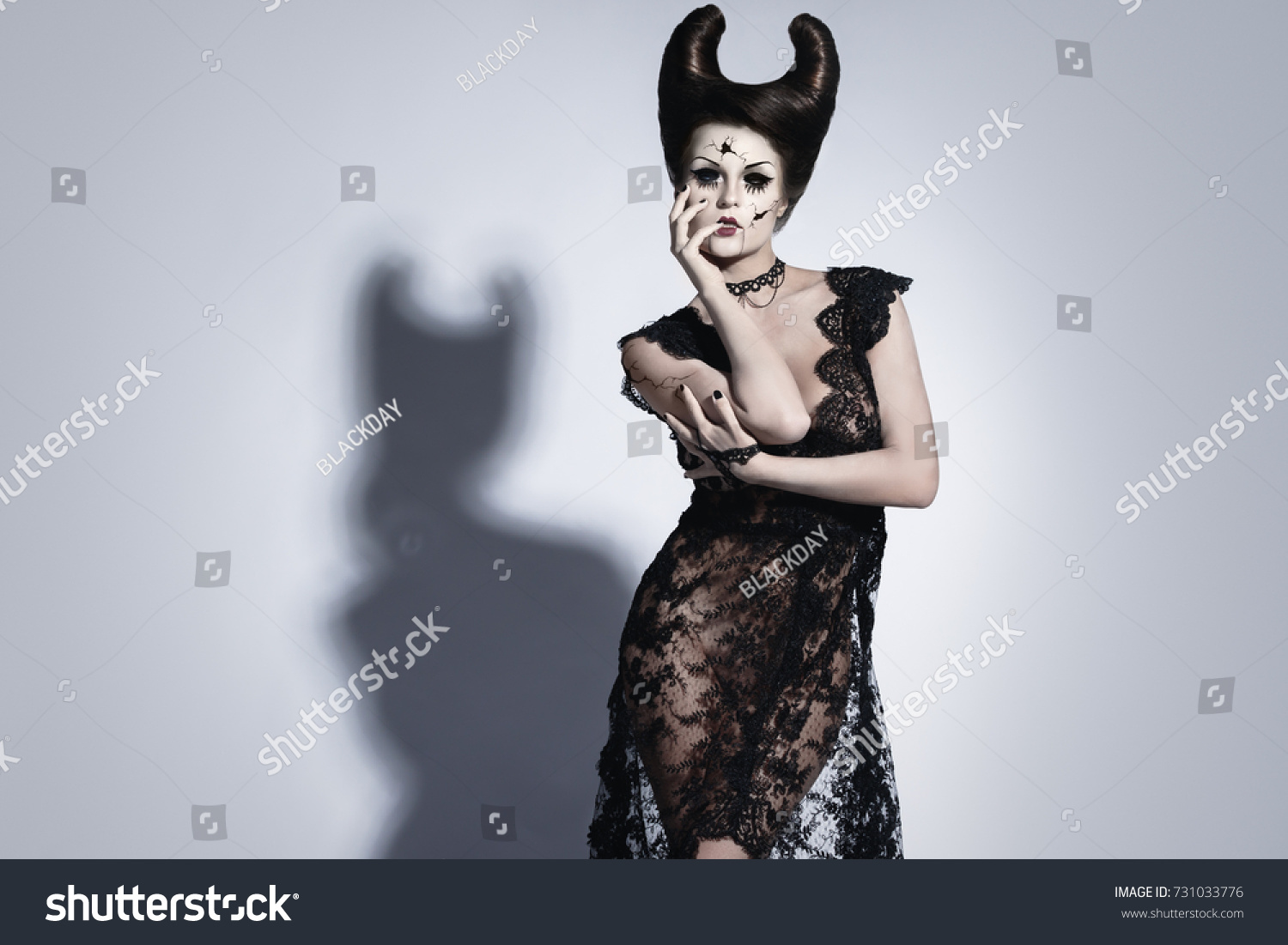 model in creative image for halloween spooky porcelain doll with horns on her head