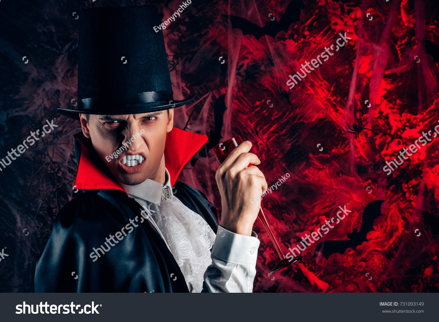 dfa36d9351 Portrait of handsome man dressed in a Dracula costume for Halloween. vampire  holds a glass