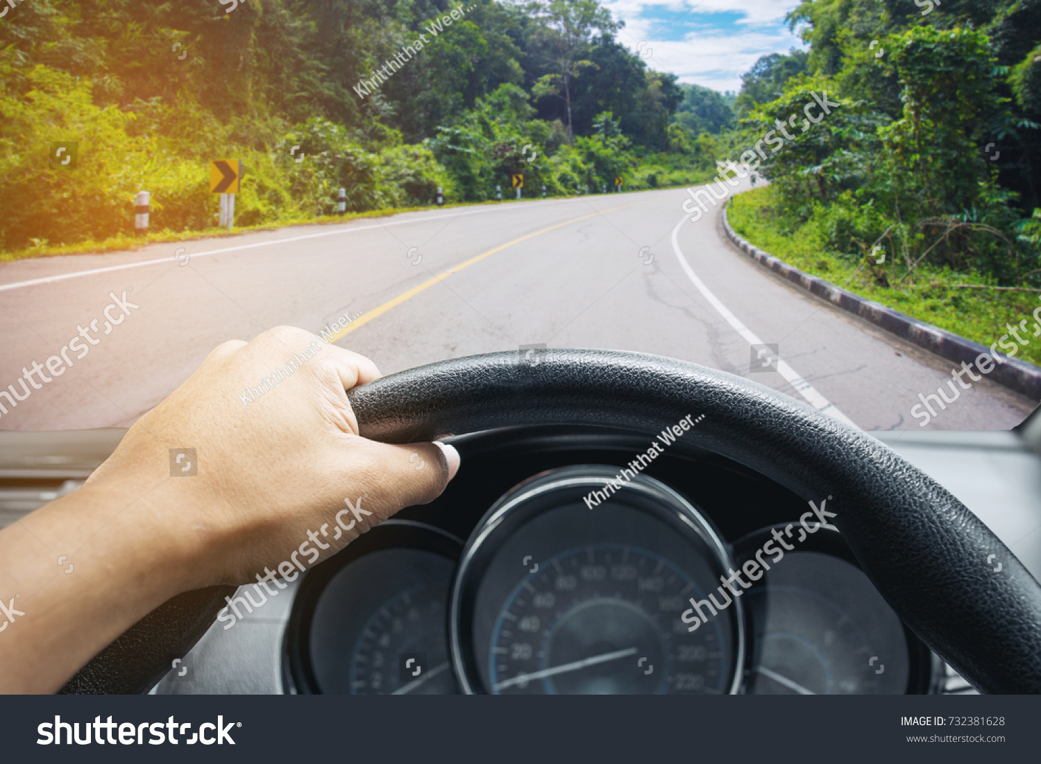 View on the dashboard of the truck driving.The driver is holding the steering wheel. Forest road is in front of the car. #732381628