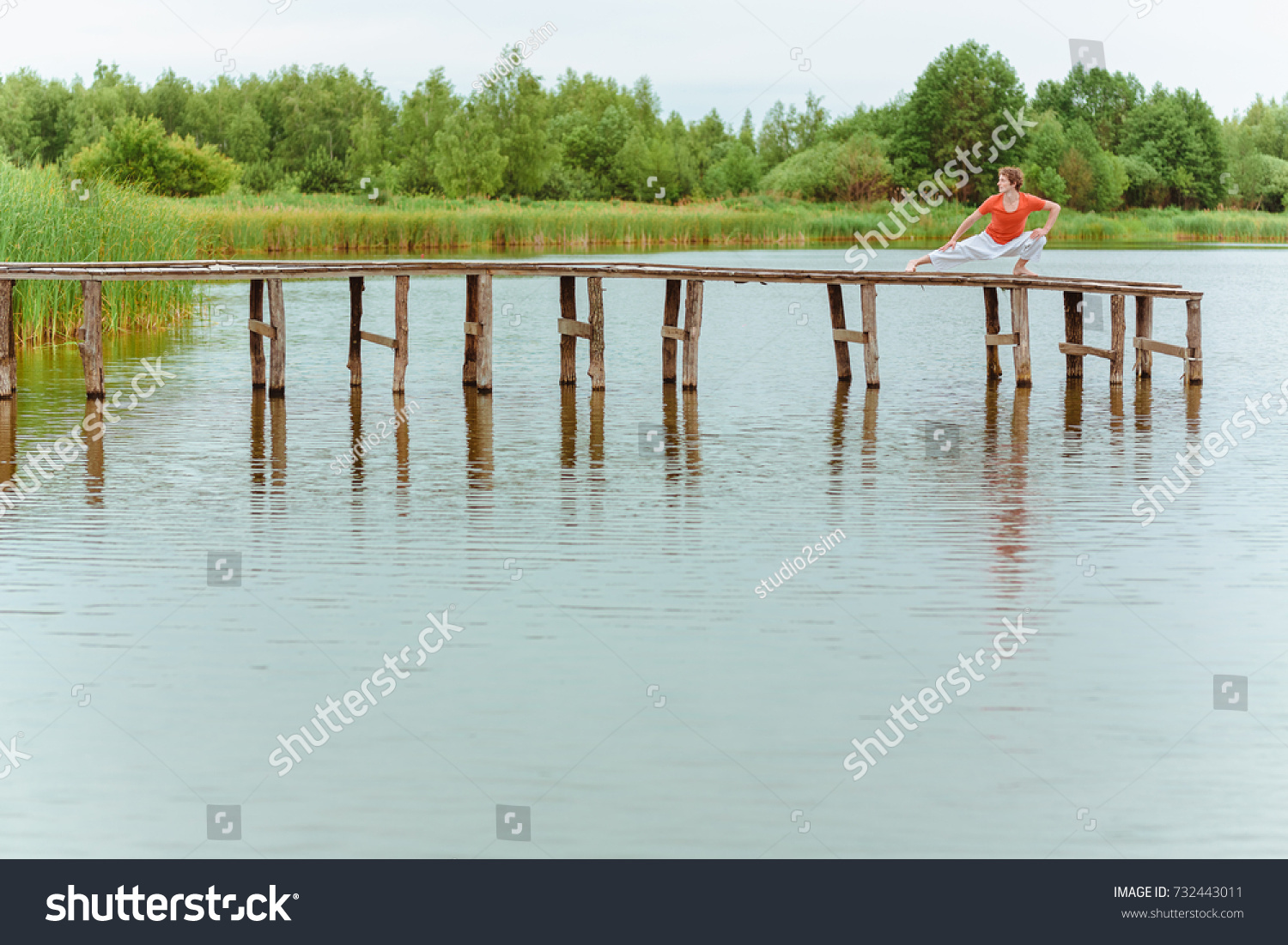 A man doing yoga on wooden pier at the lake #732443011