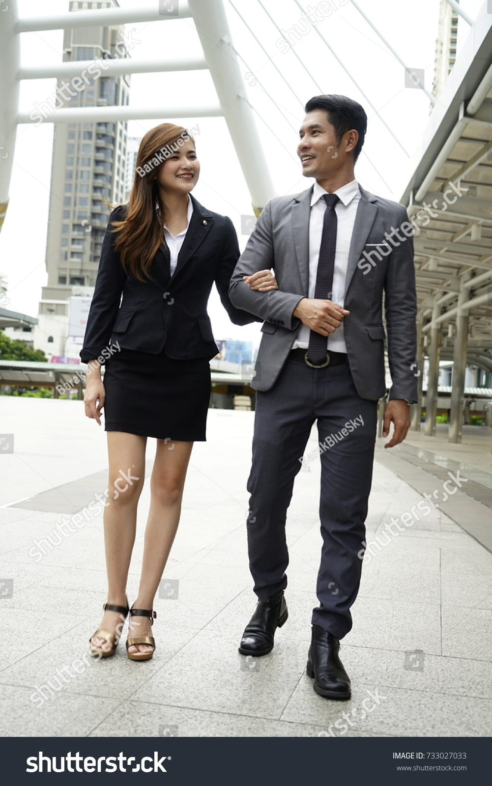 26aa1bc392 Attractive business man and woman walking and talking after work.Young  dating couple in love