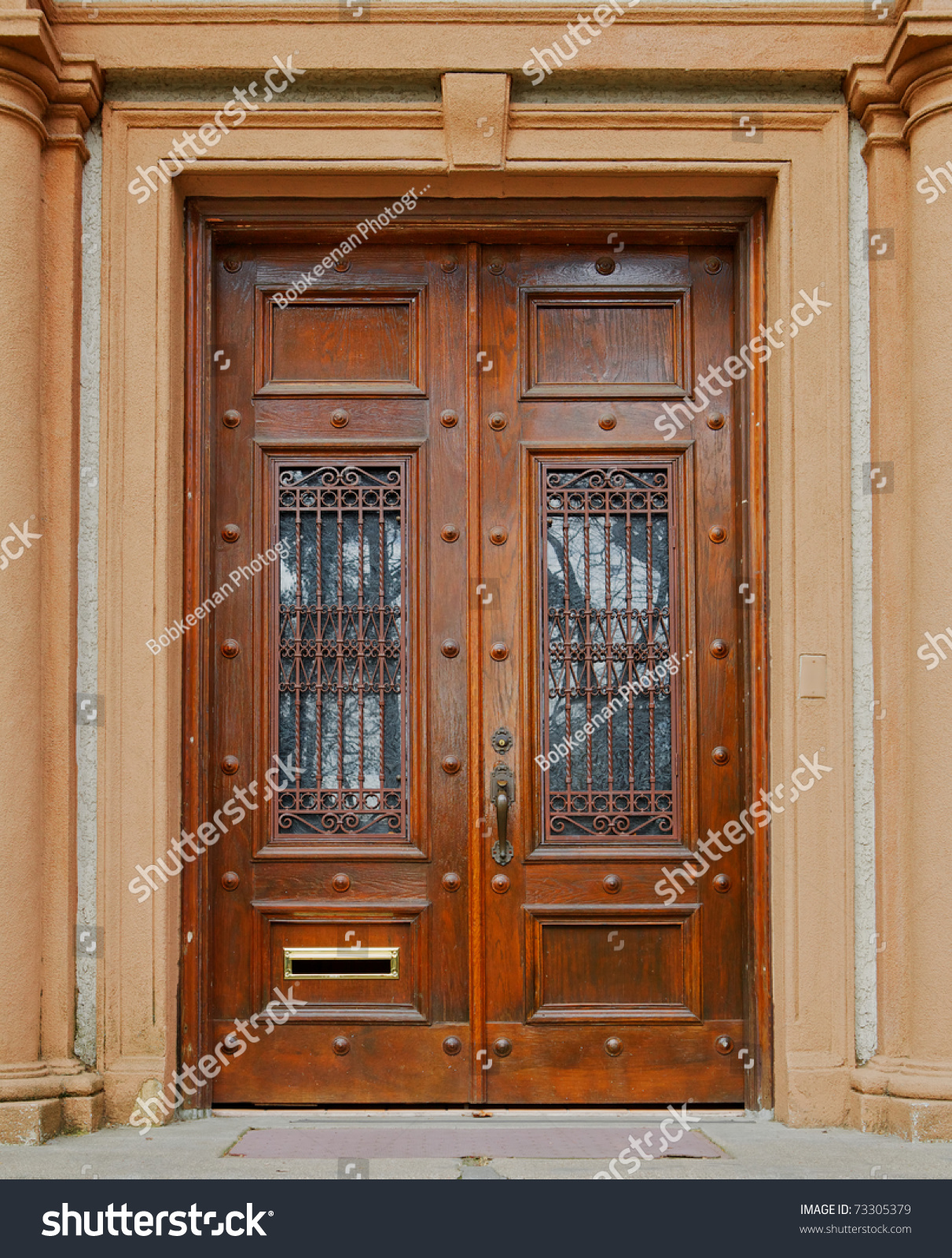 1600 #753F20 Stock Photo Ornate Stained Wood Doors With Wrought Iron Grating Over  pic Wood Doors With Wrought Iron 40111211