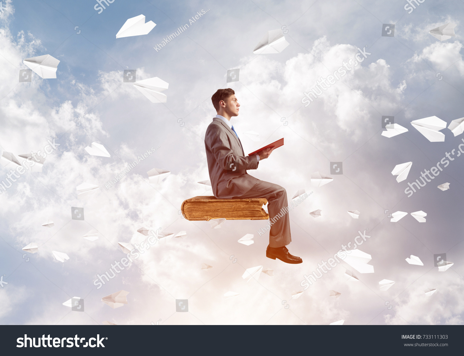 Young Businessman Sitting On Floating In Air Book With One Hands
