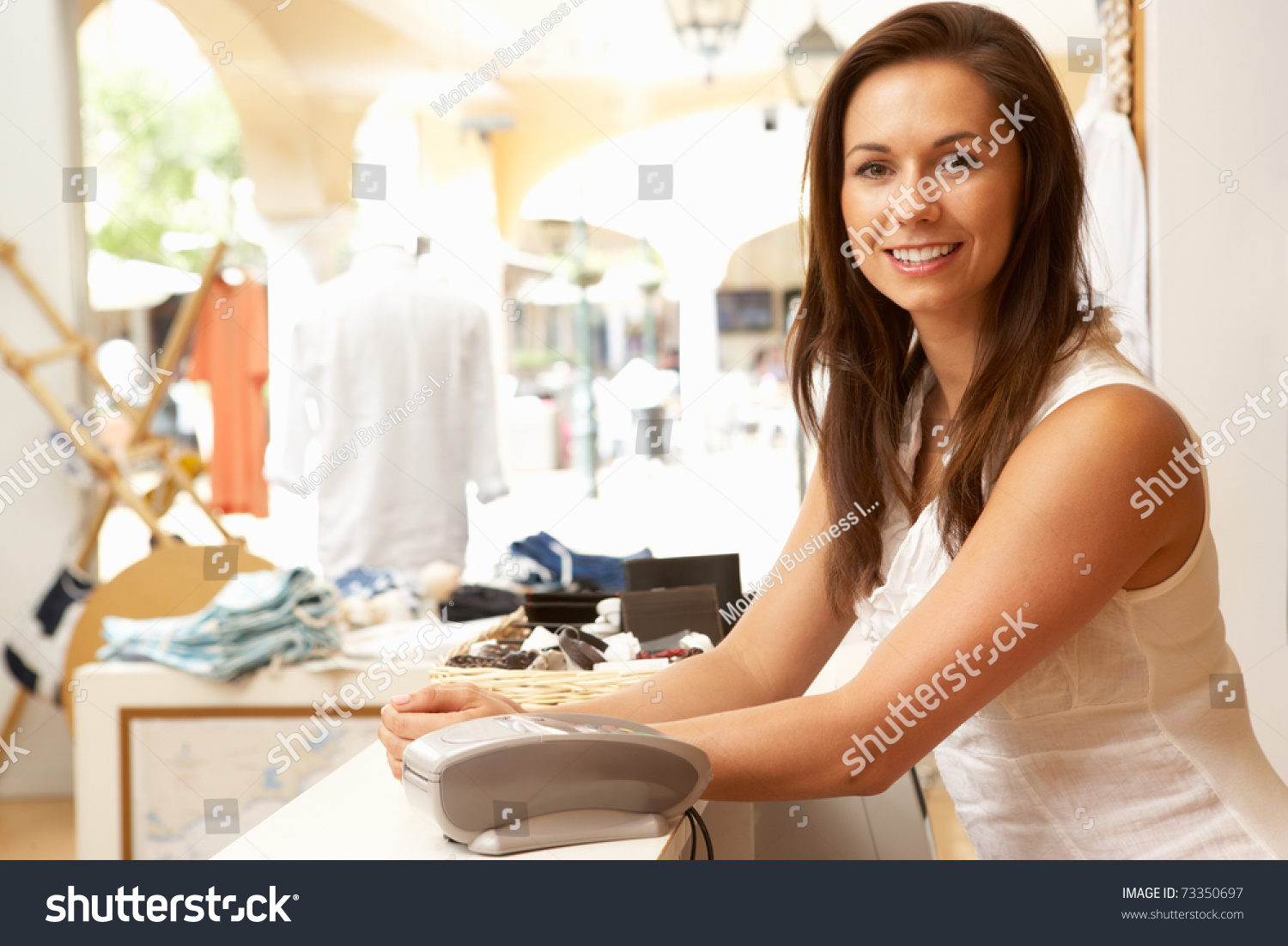 female s assistant at checkout of clothing store stock photo save to a lightbox