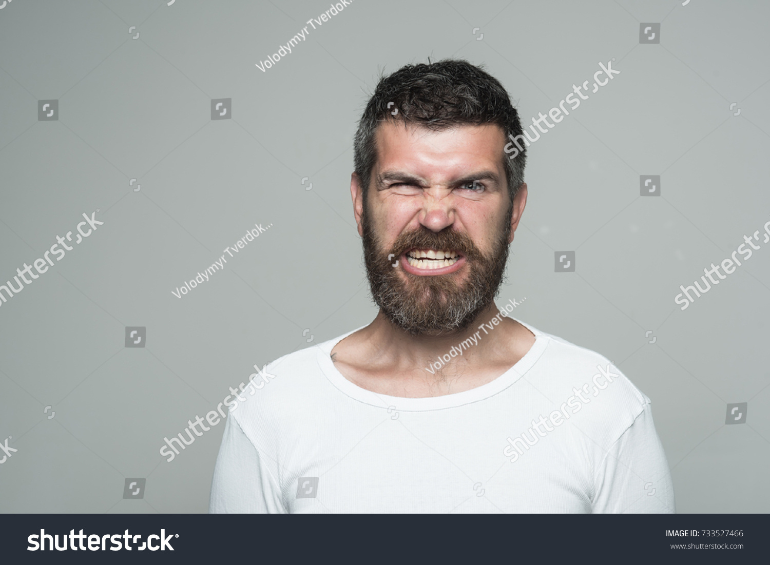 Hipster with angry face. Feeling and emotions. Guy or bearded man on grey  background