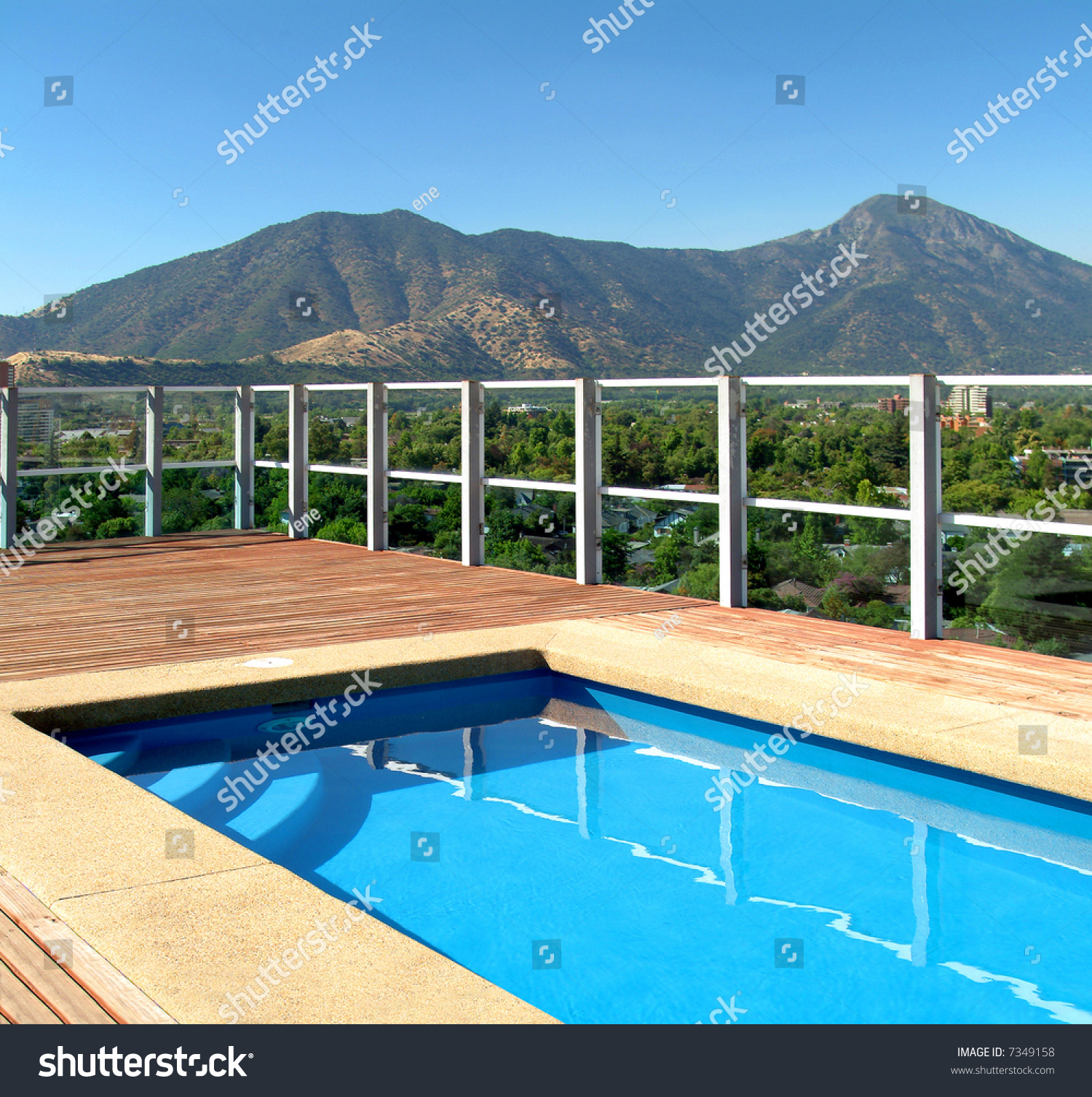 View Of A Crystal Clear Water Swimming Pool With Wood Platform And Landscape With Vegetation And