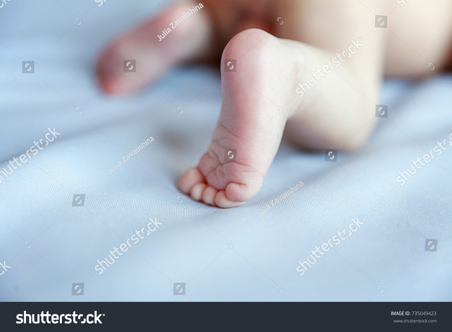 Soft newborn baby feet against a blue blanket tiny newborn babys legs closeup happy