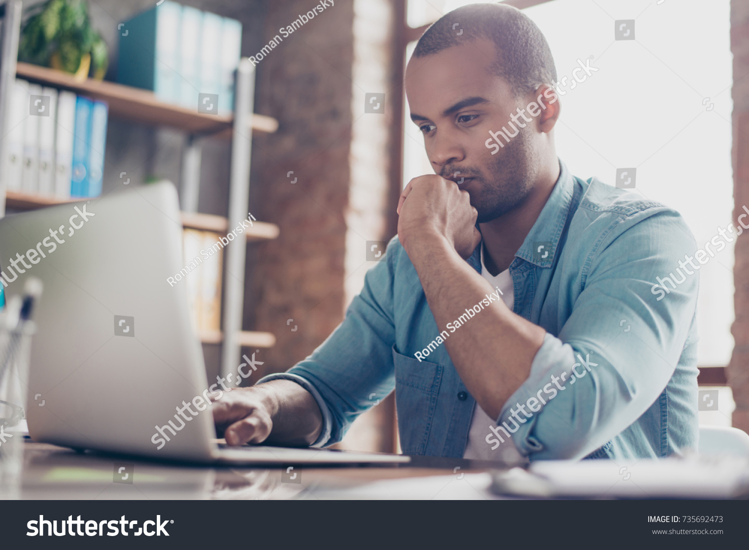 Skeptic Young Afro Freelancer Making Decision Stock Photo
