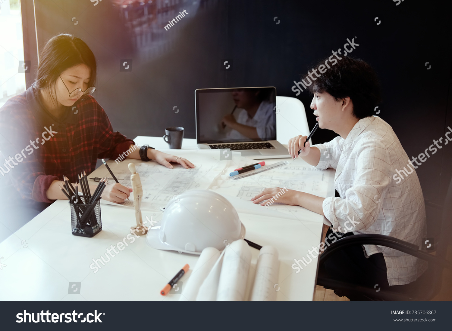 Architect working on blueprint two colleagues stock photo royalty architect working on blueprint two colleagues interior designer discussing data on blueprint on table for malvernweather Choice Image