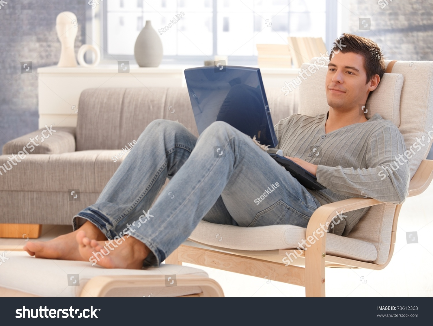 Goodlooking young man relaxing home armchair stock photo for Sitting in armchair