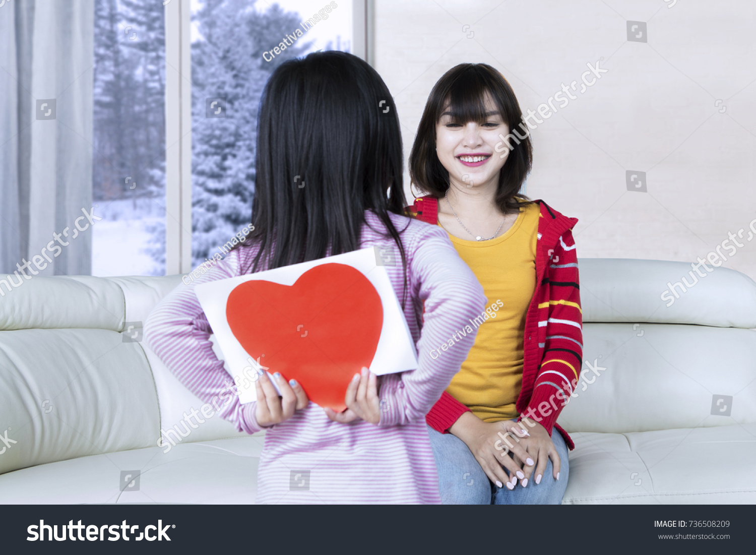 Back view little girl giving her stock photo 736508209 shutterstock back view of a little girl giving her mom a greeting card with a heart symbol buycottarizona Images