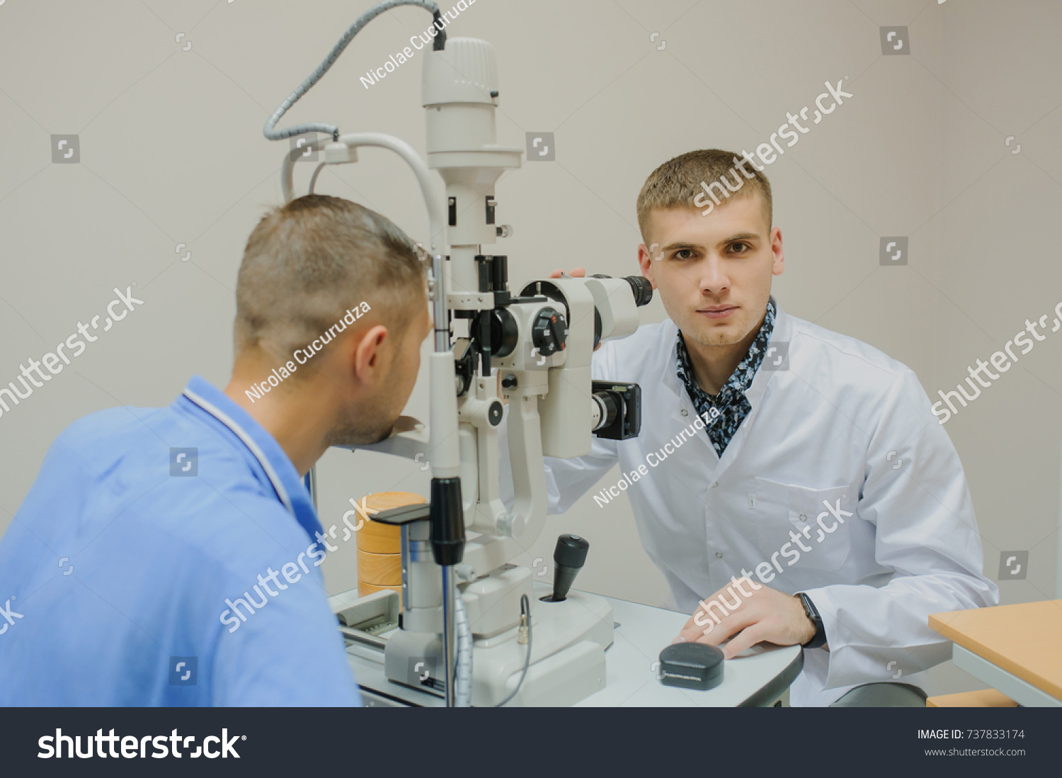 doctor/eye specialist/optometrist in an ophthalmologic clinic with a lot of medical equipment behind: biomicroscopy with slit lamp procedure, phoropter, eye scanner, non-mydriatic retinal camera #737833174