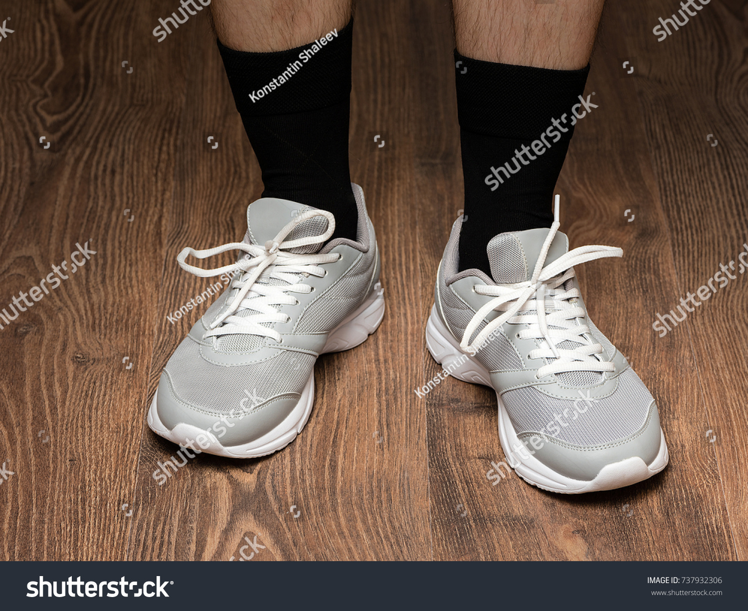 e9b5a0450b Pair of men s feet in white gray sneakers and black socks on white brown  floor background