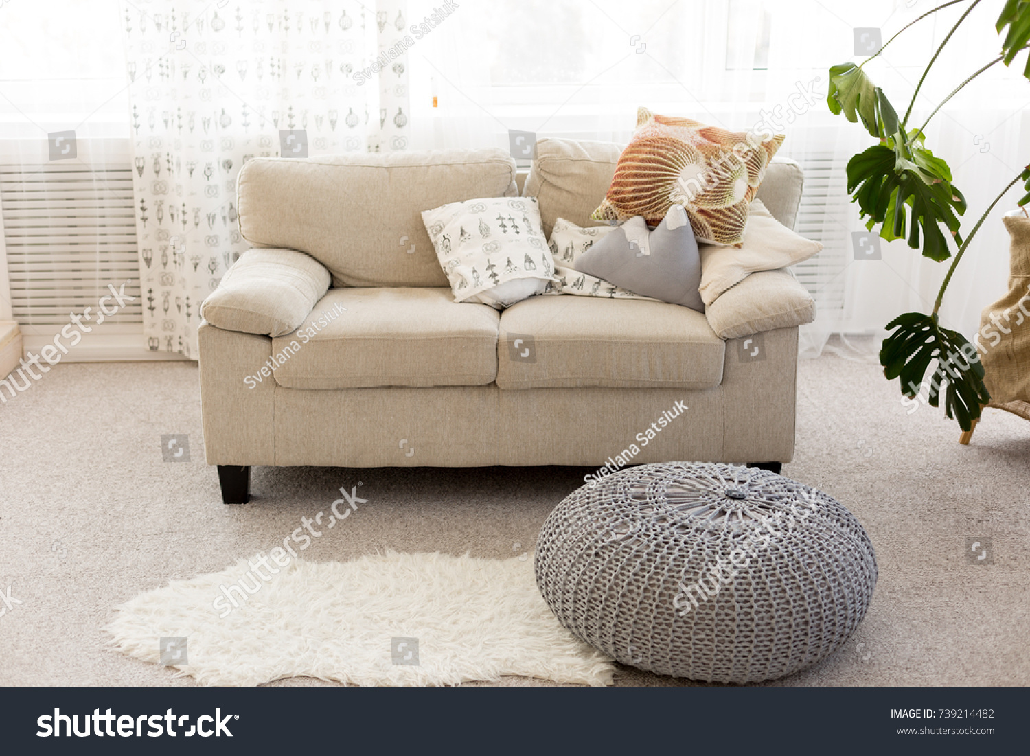 Bright Interior. Beige Sofa With Pillows And Gray Pouffe. Big Flower Room  By The