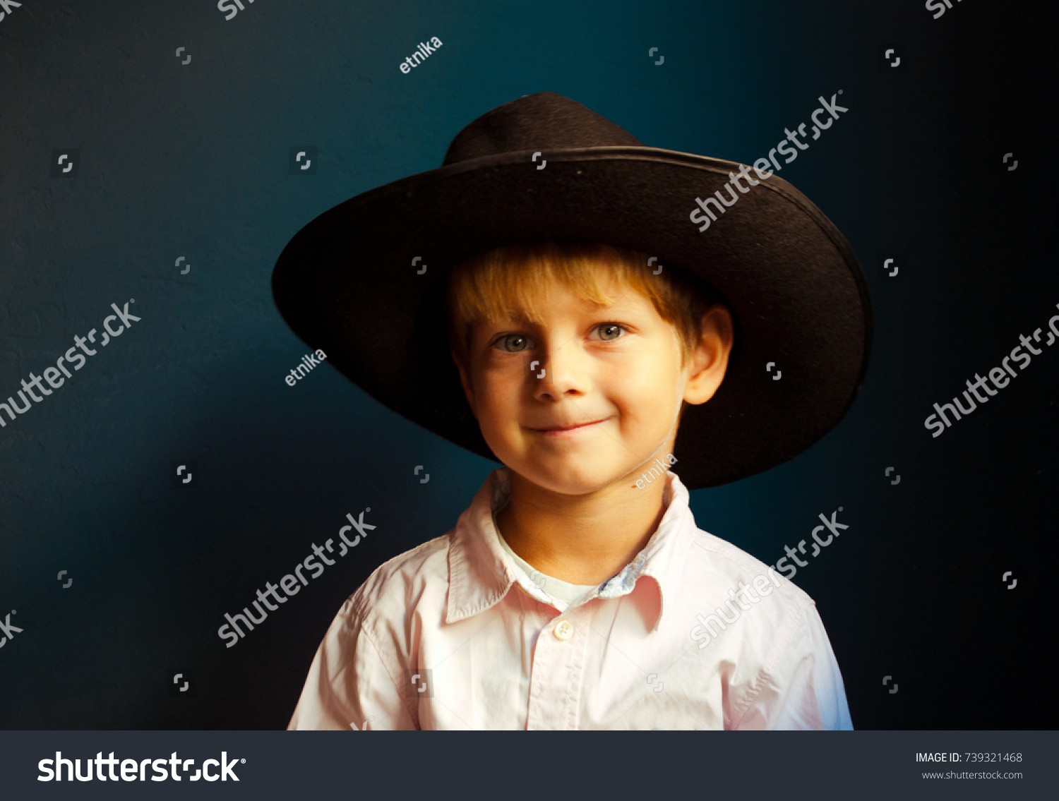 6df0cc05654 Portrait of smiling little boy in big black hat and shirt.Happy child.  Space for text.
