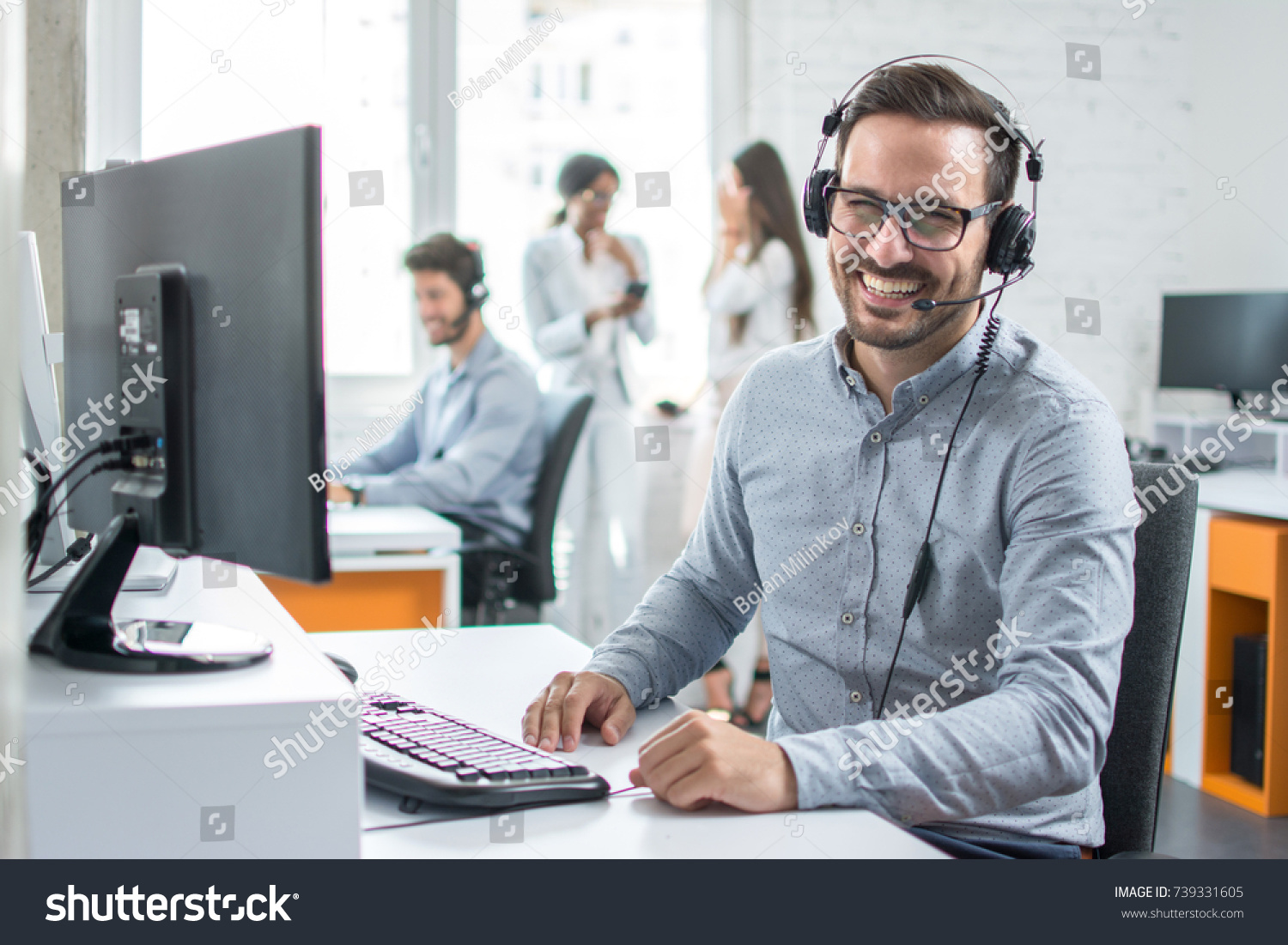 Happy young male customer support executive working in office. #739331605
