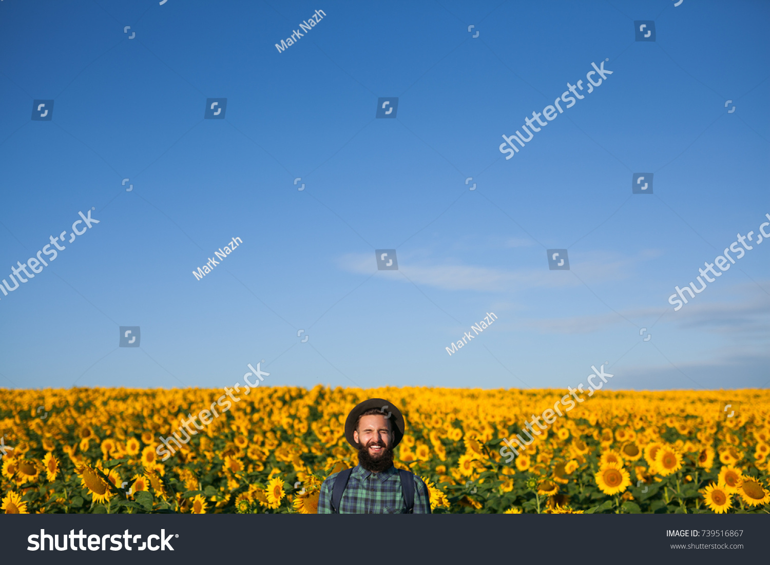 Young Hipster Man With Backpack Smiling Eyes Closed On Background Of Field Sunflowers
