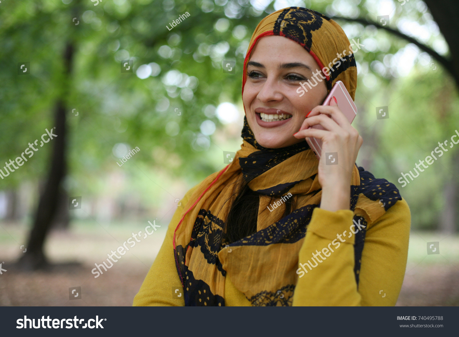Young Muslim woman talking with smart phone.  #740495788