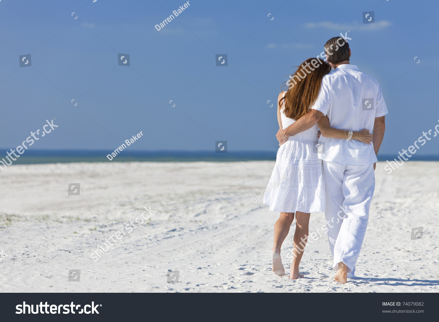e08560b18723 Rear view of man and woman romantic couple in white clothes walking on a deserted  tropical