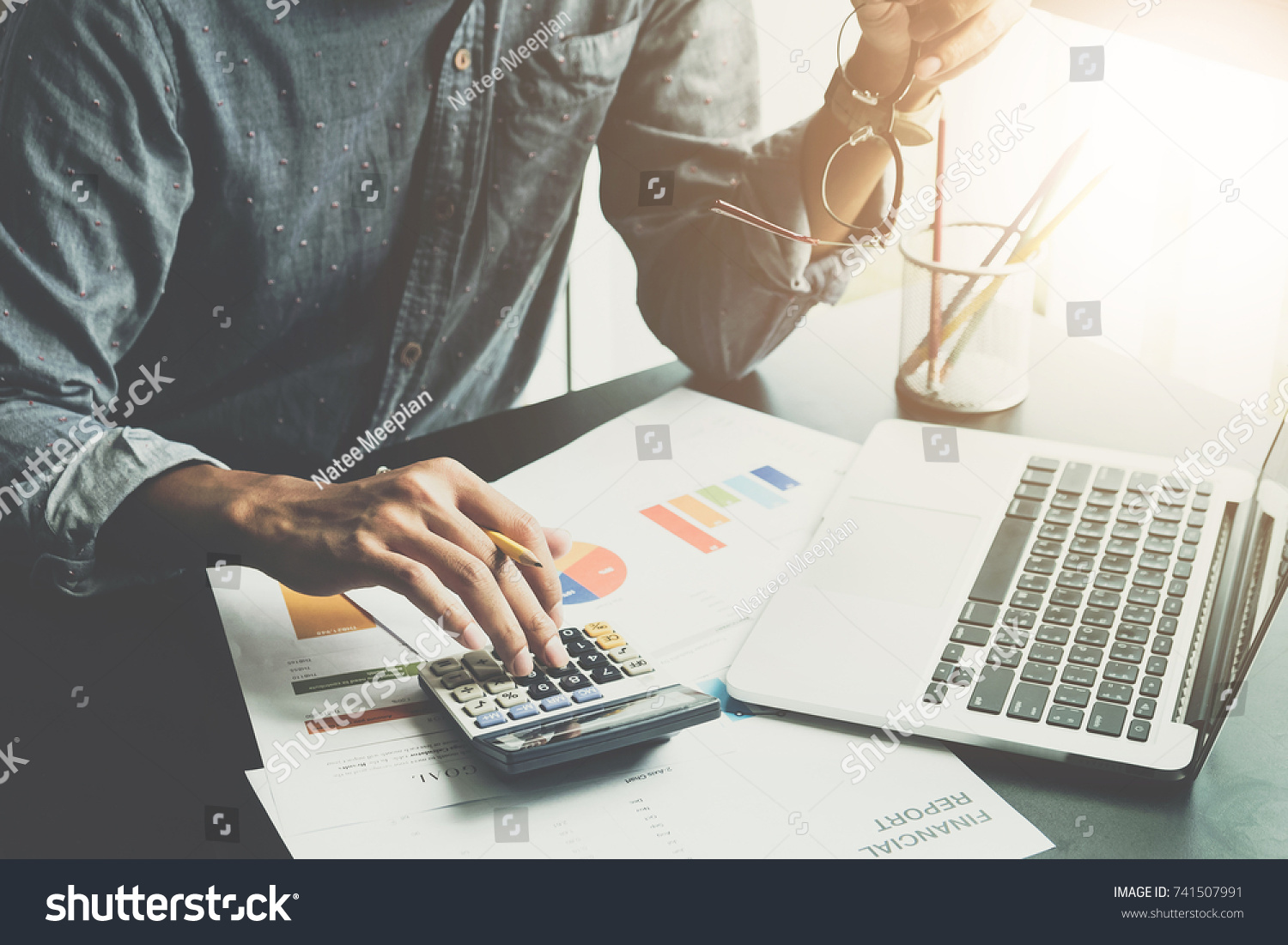 A man working about financial and analysis business document with calculator and holding glasses at his office to calculating expenses, Accounting concept #741507991