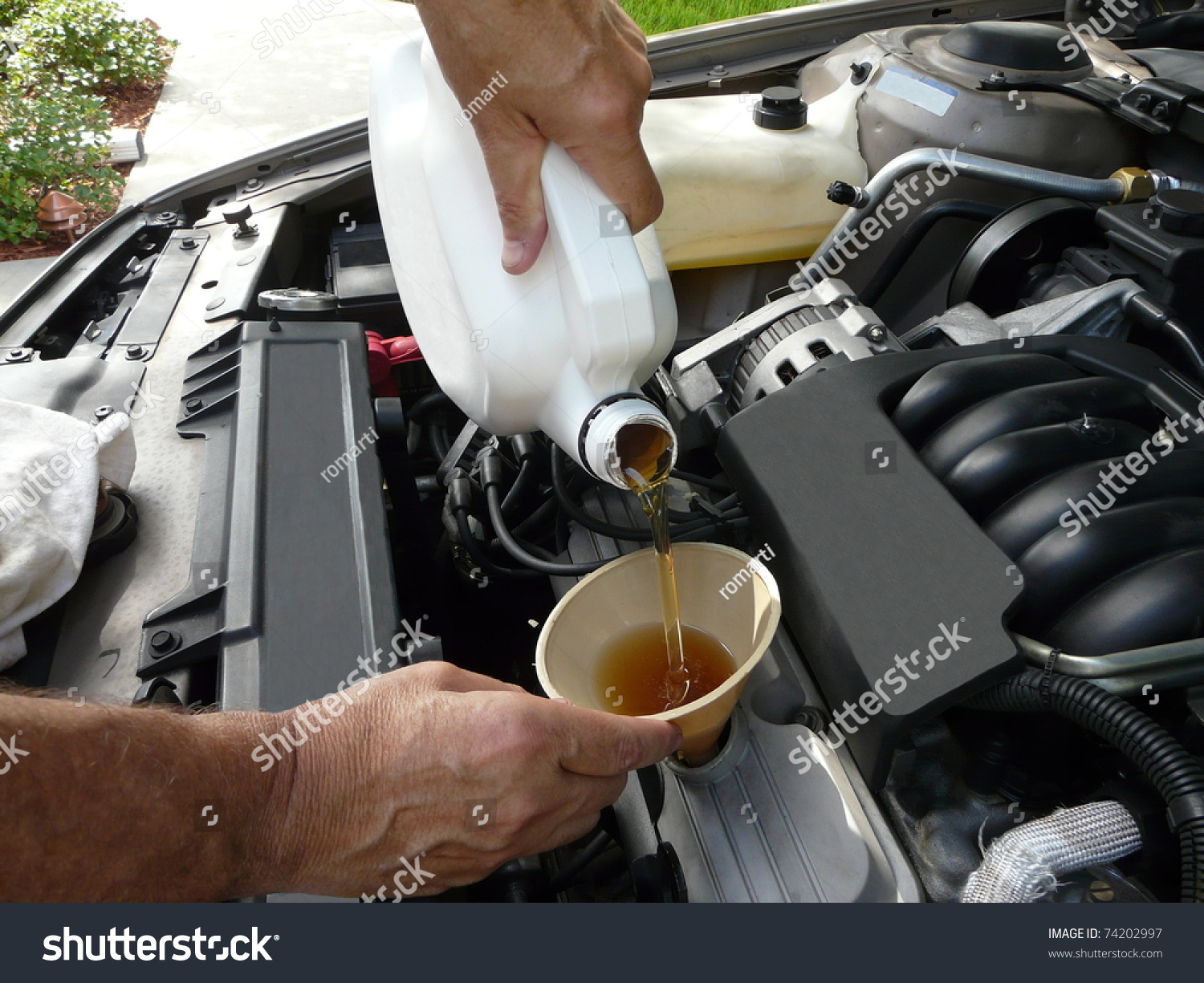 Male adding oil funnel after doityourself stock photo image male adding oil with a funnel after a do it yourself oil change solutioingenieria Gallery