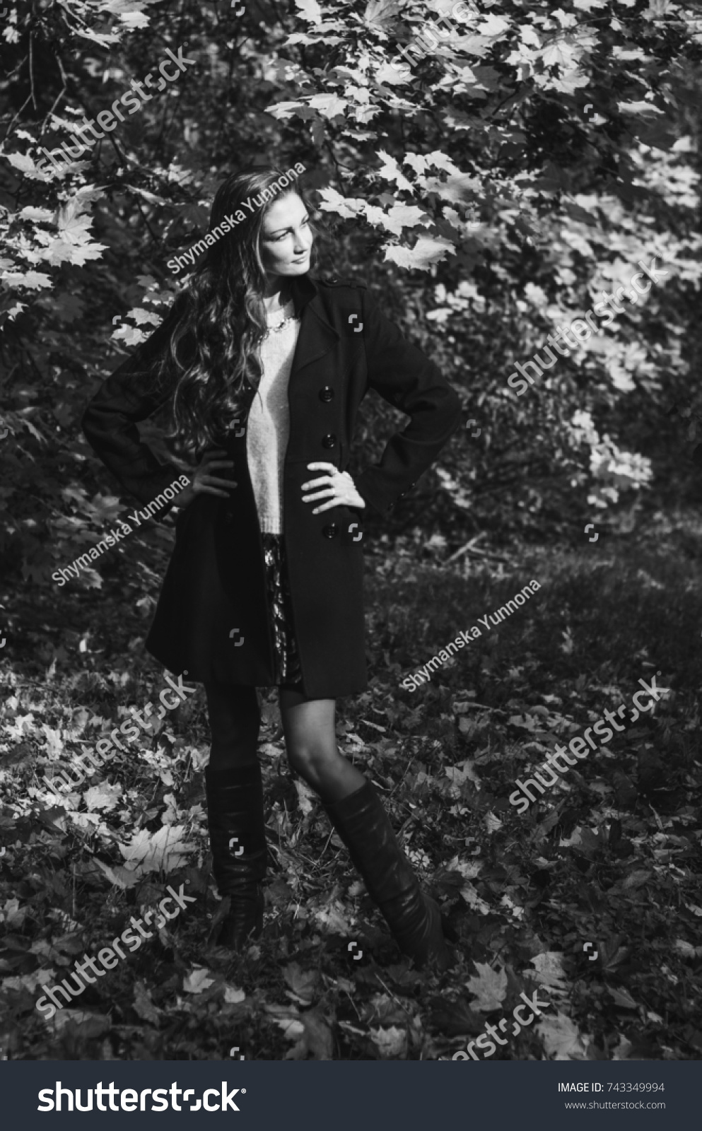f6cdaeebf Young girl in classic black coat and blue boots walks in the Park ...