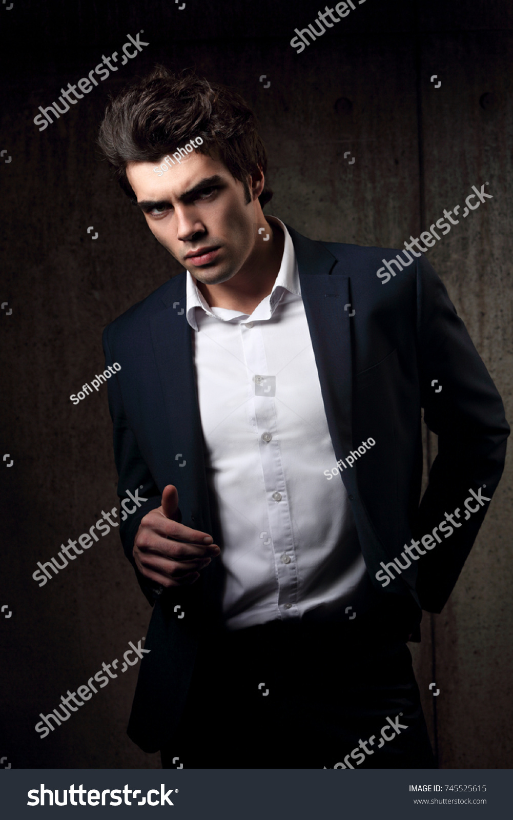d708e24c Sexy handsome male model posing in blue fashion suit and white style shirt  on dark shadow.