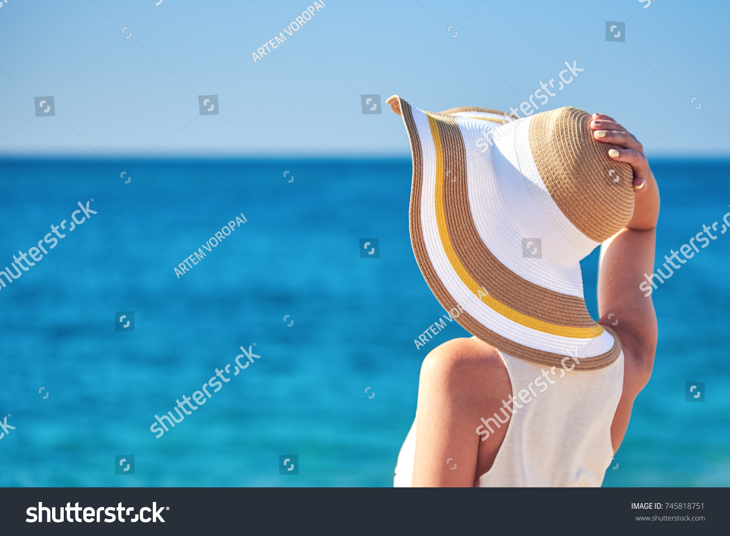 Woman in beach hat looking at the sea. #745818751