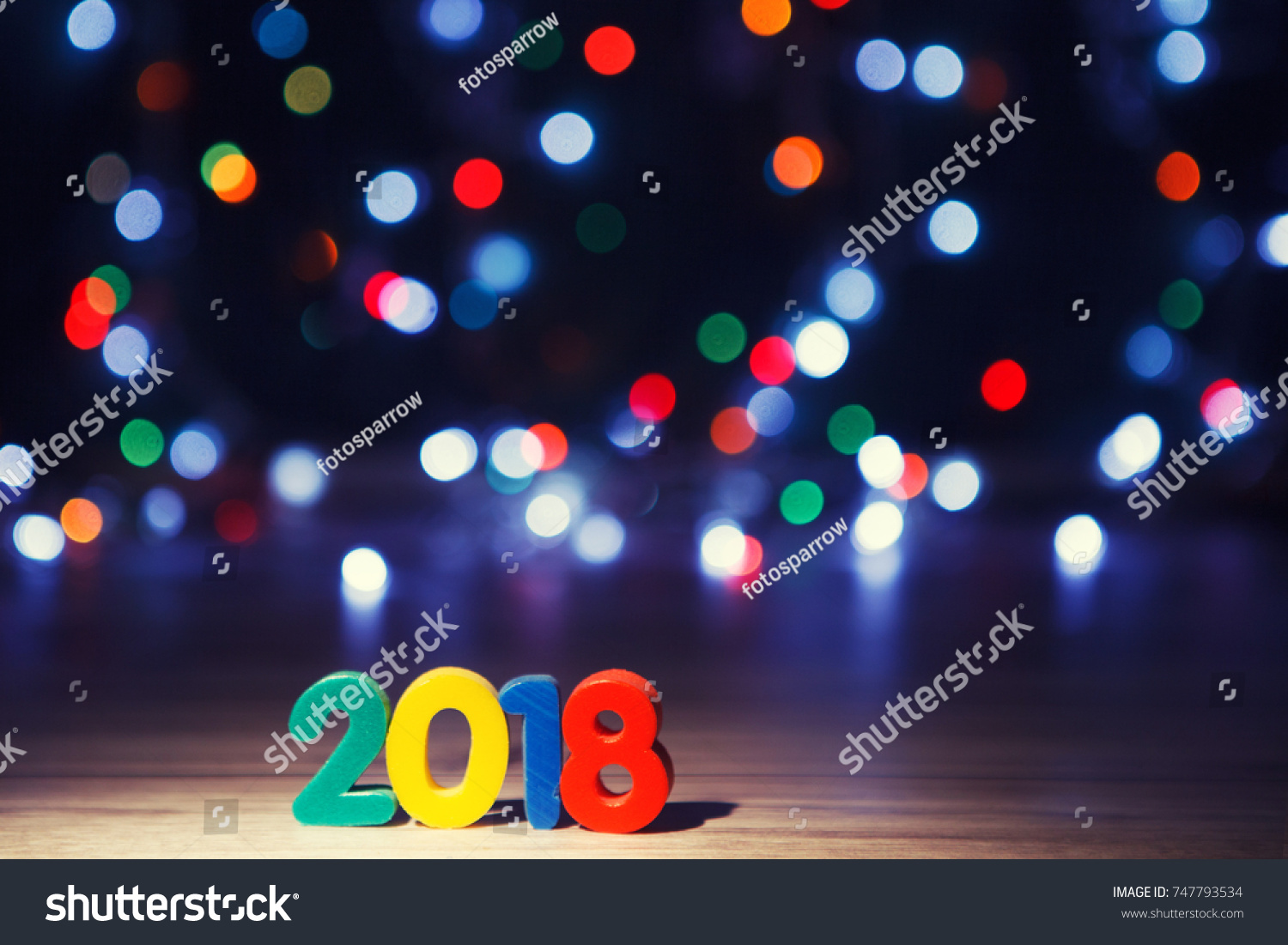 2018 written on a black background and blurred christmas lights 2018 happy new year background