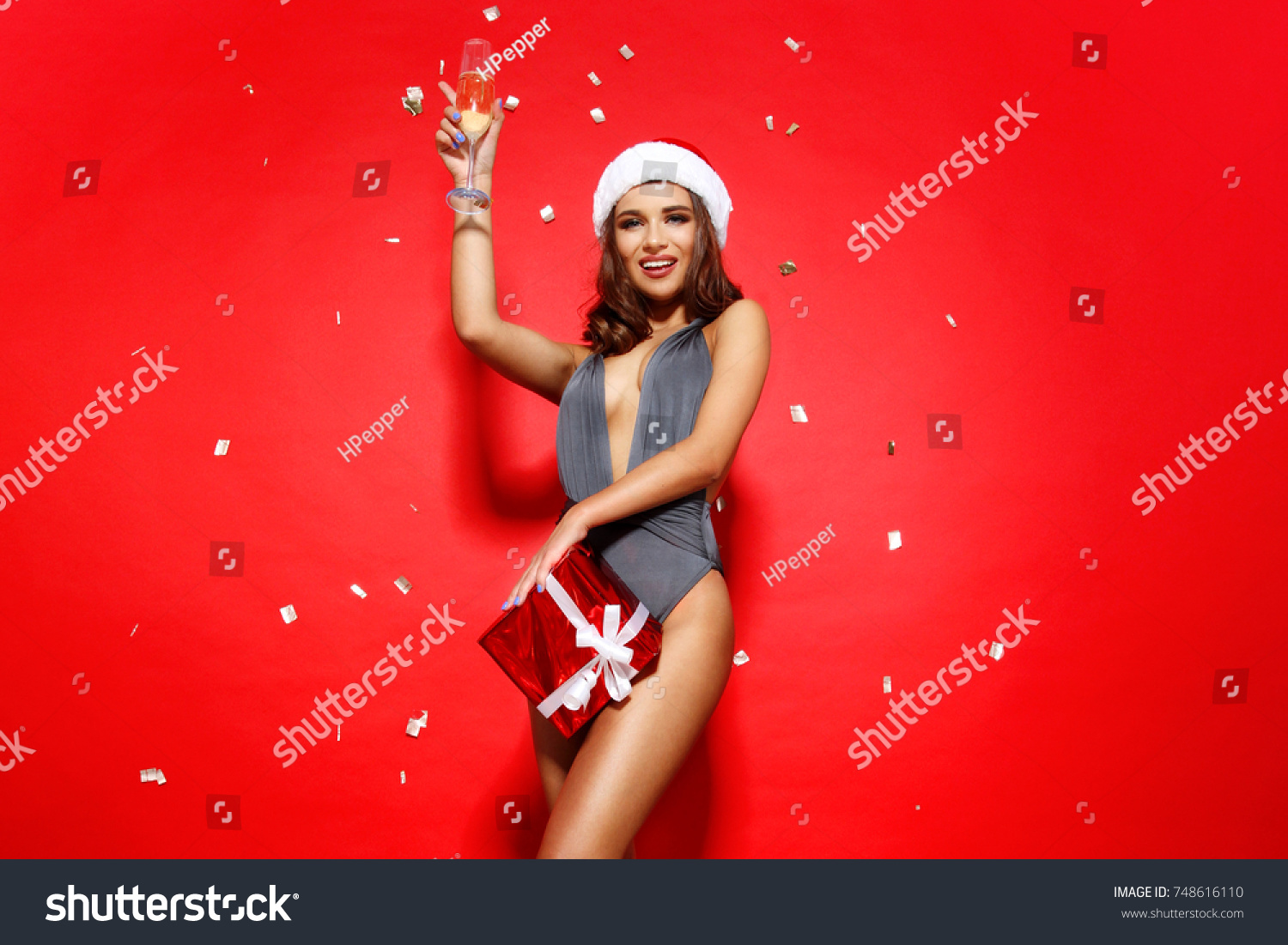 196cea35ef beautiful young girl model stands on red background in sexy bathing suit  bikini and a Christmas