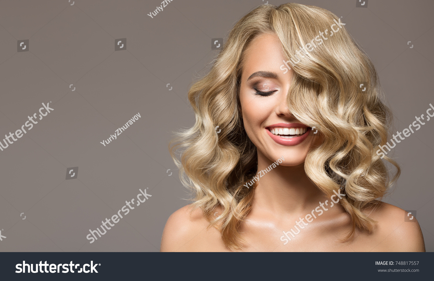 Blonde woman with curly beautiful hair smiling on gray background.  #748817557