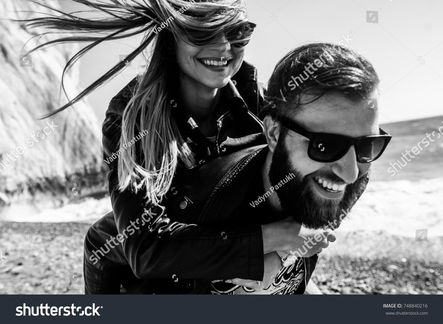 Black&white photo of happy couple in the leather jackets running on the beach #748840216