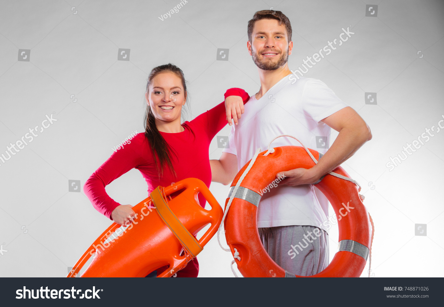 1b2b940aad0 Accident prevention and water rescue. Young man and woman lifeguard couple  on duty holding ring